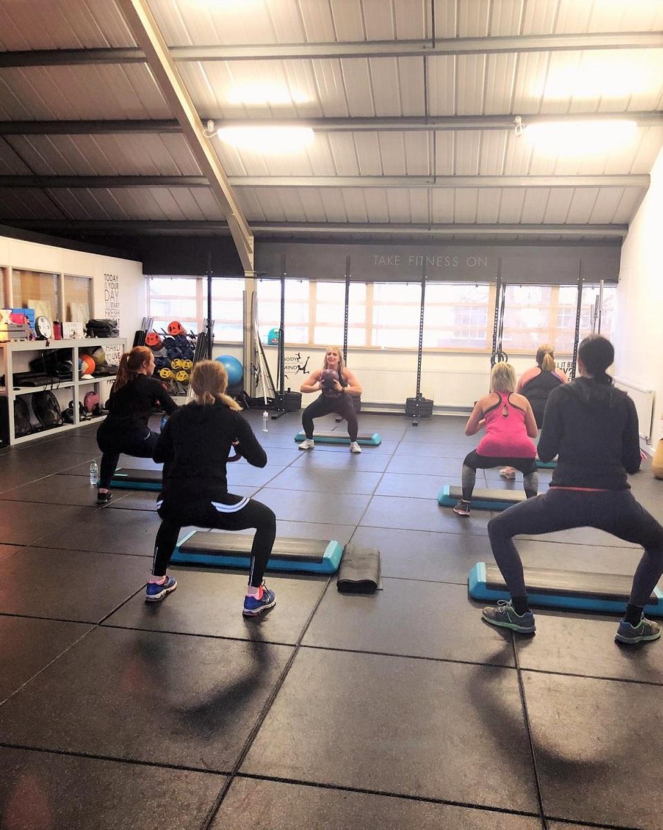 Total Tone Class goers squatting.